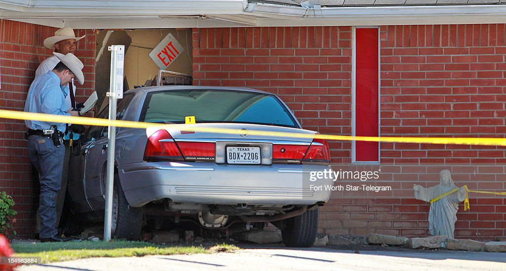 Texas Rangers investigate stand near a car that hit the Greater Sweethome Missionary Baptist Church in Forest Hill, Texas, Monday, October 29, 2012. The pastor of the church was killed when a man beat him to death at the church, according to early reports from Forest Hill police.