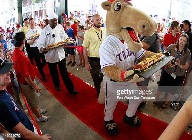 Texas Rangers mascot Captain leads the parade prior to a race to eat the 'Boomstick' a twofootlong onepound hotdog sold at Rangers Ballpark in...