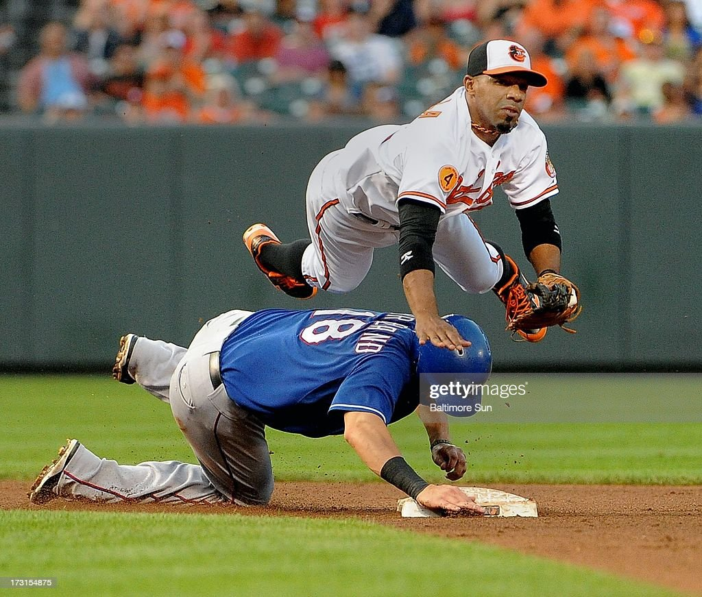 Texas Rangers' Mitch Moreland is forced out at 2nd base, as Baltimore Orioles' Alexi Casilla turns a double play during the 4th inning at Oriole Park at Camden Yards in Baltimore, Maryland, Monday, July 8, 2013.