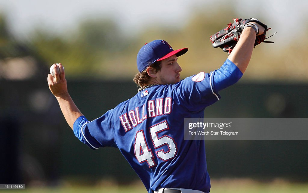 Texas Rangers pitcher <a gi-track='captionPersonalityLinkClicked' href=/galleries/search?phrase=Derek+Holland+-+Baseball+Player&family=editorial&specificpeople=8003703 ng-click='$event.stopPropagation()'>Derek Holland</a> warms up for a training camp workout in Surprise, Az., on Sunday, Feb. 22, 2015.