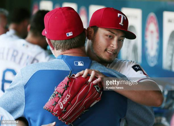 Texas Rangers pitcher Yu Darvish is hugged by pitching coach Doug Brocail in the dugout after working eight solid innings in a 52 win over the Kansas...