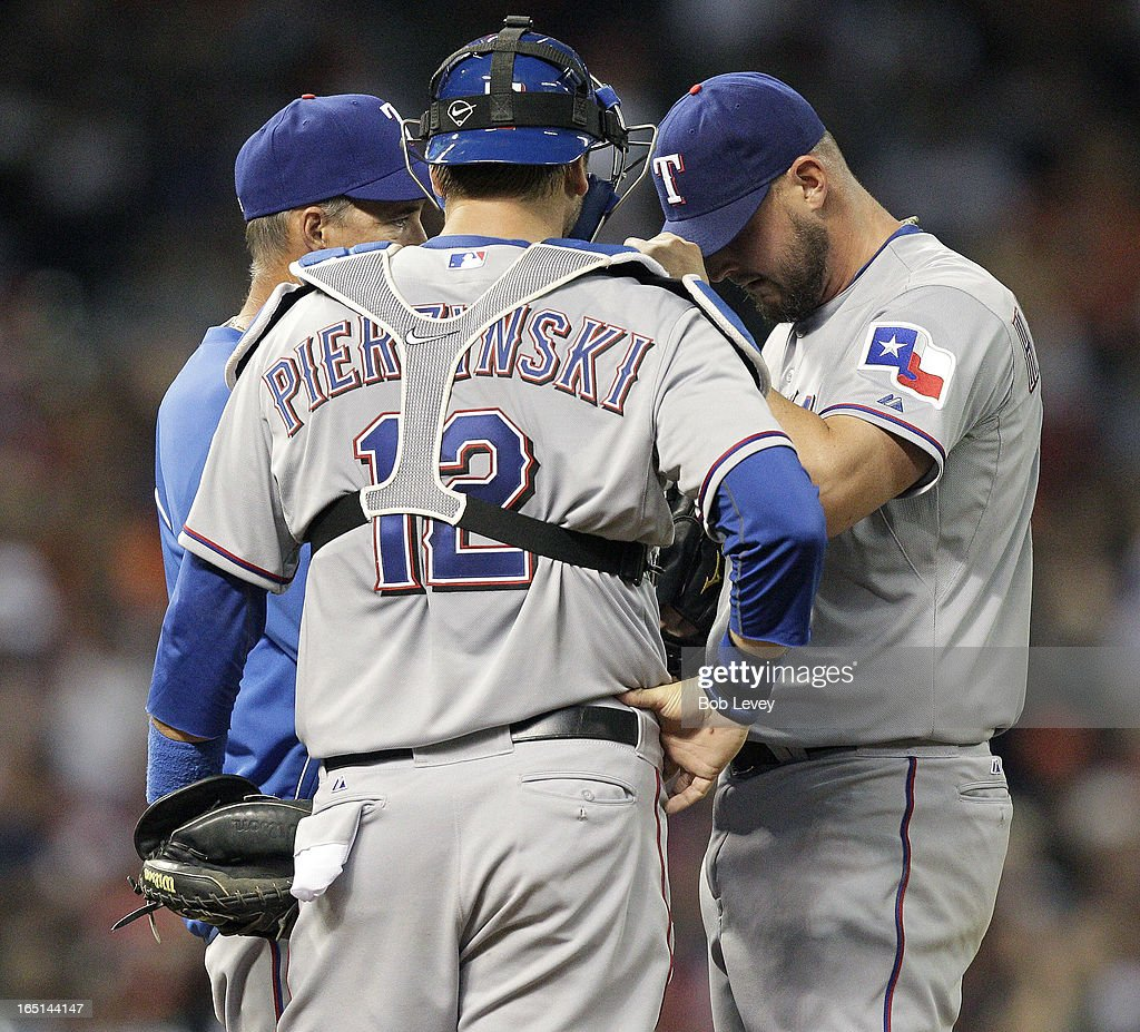 Texas Rangers pitching coach talks with Matt Harrison #54 of the Texas Rangers and A.J. Pierzynski #12 of the Texas Rangers on Opening Day at Minute Maid Park on March 31, 2013 in Houston, Texas.