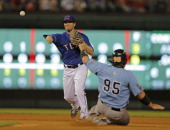 Texas Rangers second baseman Donnie Murphy turns a double play in the fourth inning as Tigres de Quintana Roo's Karim Garcia slides into second base...