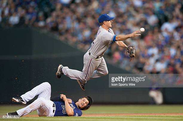 Texas Rangers second baseman Josh Wilson turns a double play after tagging Colorado Rockies third baseman Nolan Arenado out on the base path during a...