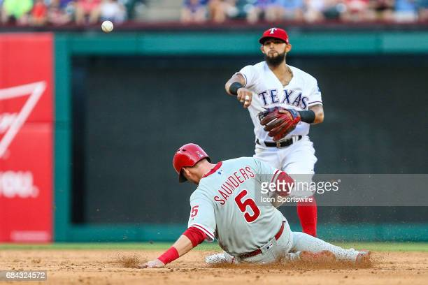 Texas Rangers second baseman Rougned Odor steps on the bag for a double play as Philadelphia Phillies right fielder Michael Saunders slides into...