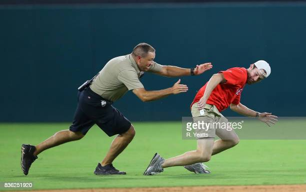 Texas Rangers security guards chase down a fan on the field in the ninth inning against the Chicago White Sox at Globe Life Park in Arlington on...