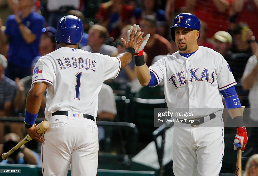 Texas Rangers shortstop Elvis Andrus gets a high five from designated hitter Carlos Beltran as he scores on a single in the fifth inning against the...