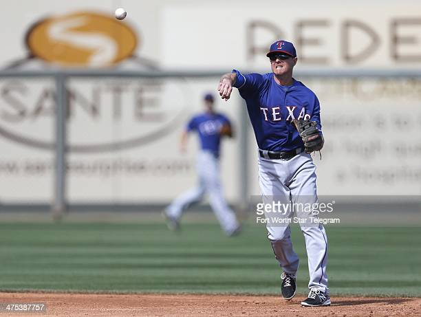 Texas Rangers shortstop Josh Wilson throws to first in the third inning against the Kansas City Royals during a Cactus League game in Surprise Ariz...