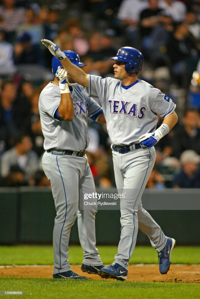 Texas Rangers' Shortstop Michael Young gets a highfive from teammate Gerald Laird after hitting a 3run homer during the game against the Chicago...