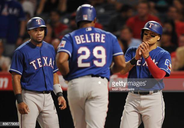 Texas Rangers third baseman Adrian Beltre is greeted at home plate by shortstop Elvis Andrew and designated hitter ShinSoo Choo after Beltre hit a...