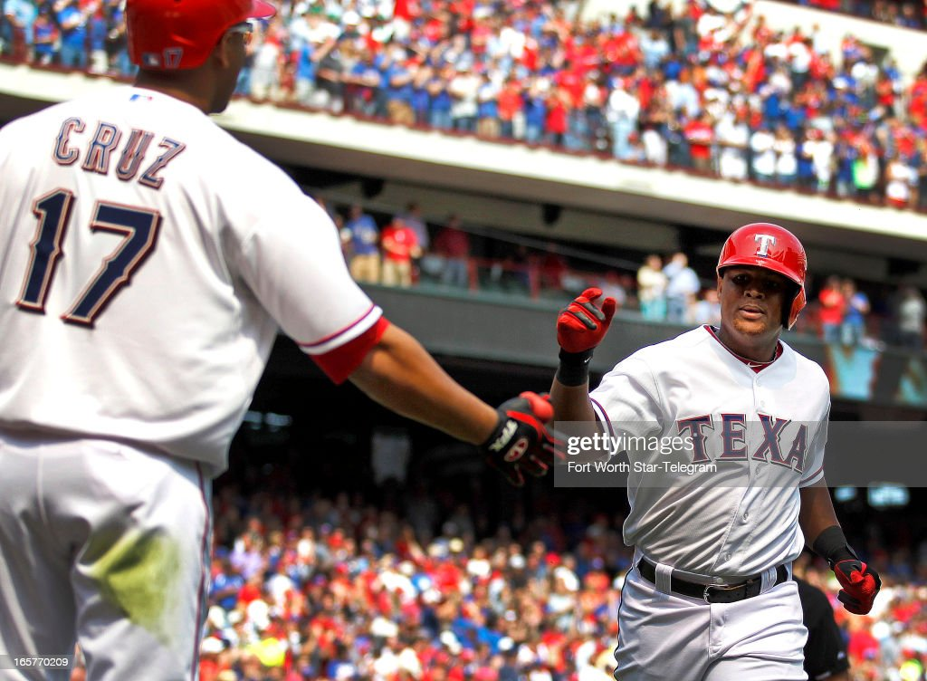 Texas Rangers third baseman Adrian Beltre (right) is welcomed home by Texas Rangers right fielder Nelson Cruz (17), after Beltre hit a home run in the seventh inning against the Los Angeles Angels at Rangers Ballpark in Arlington, Texas, Friday, April 5, 2013. The Rangers defeated the Angels 3-2.