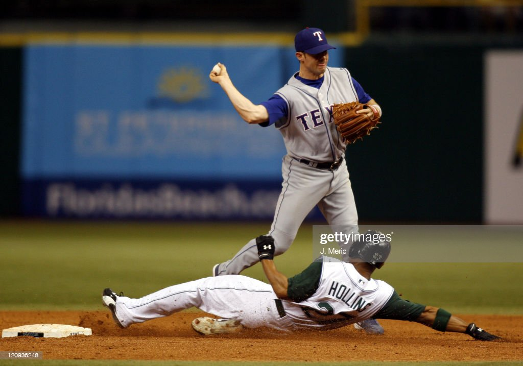 Texas shortstop Michael Young turns the double play over Tampa Bay's Damon Hollins for the final outs in Tuesday night's game at Tropicana Field in...