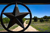 An iron Texas Star welded into a ranch gate makes a perfect frame to showcase the landscape of the Texas Hill Country ranch that unfolds behind.