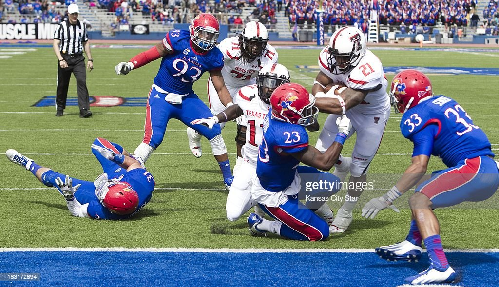 Texas Tech Red Raiders running back DeAndre Washington (21) battles his way into the end zone as Kansas Jayhawks safety Dexter Linton (23) and Kansas linebacker Cassius Sendish (33) try to stop him during the second half at Memorial Stadium in Lawrence, Kansas, Saturday, October 5, 2013. Texas Tech defeated Kansas, 56-16.