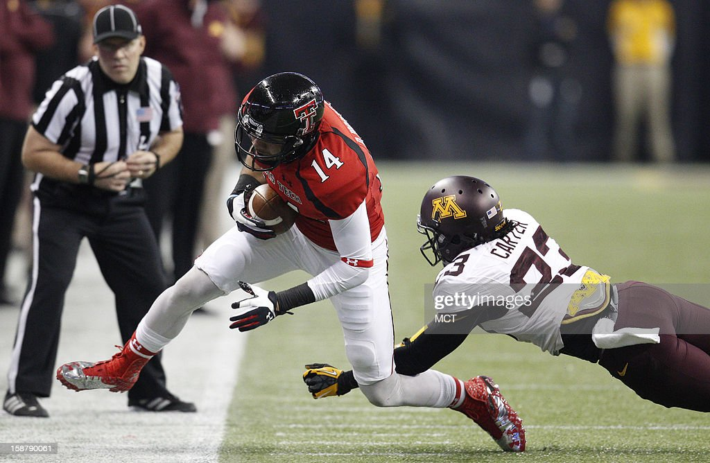 Texas Tech's Darrin Moore (14) beats Minnesota's Michael Carter on a first-down reception during the second quarter of the Meineke Car Care Bowl of Texas on Friday, December 28, 2012, at Reliant Stadium in Houston, Texas.