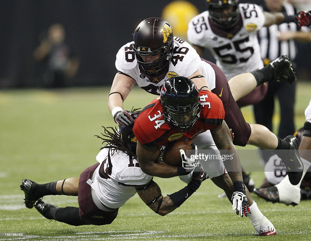 Texas Tech's Kenny Williams (34) drags Minnesota's Derrick Wells and Cameron Botticelli for a first down during the second quarter of the Meineke Car Care Bowl of Texas on Friday, December 28, 2012, at Reliant Stadium in Houston, Texas.