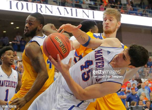 TexasArlington's Jorge Bilbao struggles to control a rebound against Cal State Bakersfield's James Suber and Brent Wrapp late in the game in a...