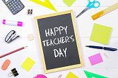 Text chalk on a chalkboard: Happy Teacher's Day. School supplies, office, books, apple