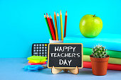 Text chalk on a chalkboard: Happy Teacher's Day. School supplies, office, books, apple