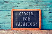 a wooden-framed chalkboard with the text closed for vacation written in it, on a rustic wooden surface, against a blue wooden background