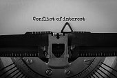 Text Conflict of interest typed on retro typewriter
