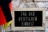 closeup of a chalkboard with the text Tag der Deutschen Einheit, Day of German Unity written in German, and some flags of Germany against a rustic wooden background