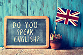 a chalkboard with the text do you speak english? written in it, a pot with pencils and the flag of the United Kingdom, on a wooden desk, with a filter effect