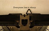 Text Everyone has a story typed on retro typewriter