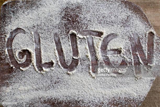text GLUTEN written on powdered cutting board