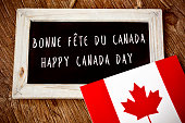 the text Happy Canada Day written in French and English in a chalkboard, and a flag of Canada, on a rustic wooden surface