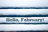 Text Hello February on old wood texture with snow.