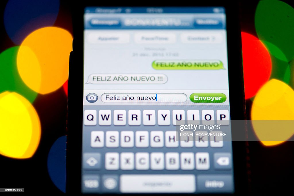A text message (SMS) of New Year greetings in Spanish is pictured on a smartphone on December 31, 2012 in Paris. Millions of SMS should be sent in the world on January 1, 2013. AFP PHOTO LIONEL BONAVENTURE