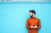 Smiling man leaning on the colorful wall while using mobile phone