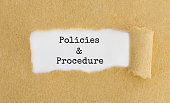 Text Policies and Procedure appearing behind ripped brown paper.