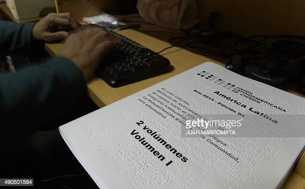 A text printed in braille is seen next to a man working with a digital audio book in a computer at 'Tiflolibros' which offers an online library for...