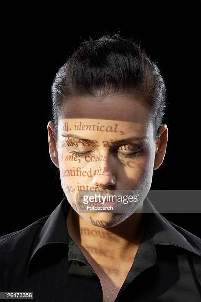 Text projected on woman's face, eyes closed