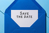Text Save the date on white paper at blue envelope. business concept.
