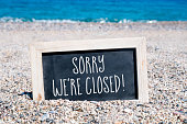 a wooden-framed chalkboard with the text sorry we are closed written in it, placed on the sand of a beach, with the sea in the background