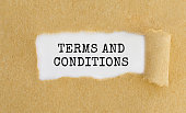 Text Terms And Conditions appearing behind ripped brown paper.