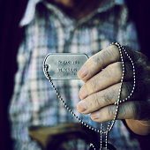 closeup of an old caucasian man showing a dog tag with the text thank you veterans engraved in it
