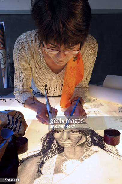 A textile craft specialist shows the Engraving stage the first involved in preparing a scarf for print at a presentation at the Nissim de Camondo...
