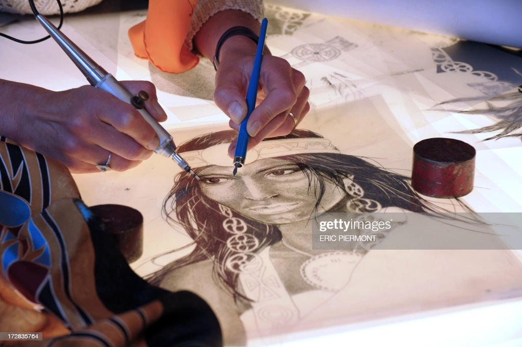 A textile craft specialist shows the Engraving stage, the first involved in preparing a scarf for print at a presentation at the Nissim de Camondo Museum in Paris on July 4, 2013 of textile crafts at French luxury goods group Hermes. During Haute Couture presentations, as parto of the metiers d'arts workshops, Hermes Texile Holding based in Lyon, presents five textile crafts, Engraving, Frame-printing or Lyonnaise printing, warp printing, hand-cut silk au Sabre and Linking.