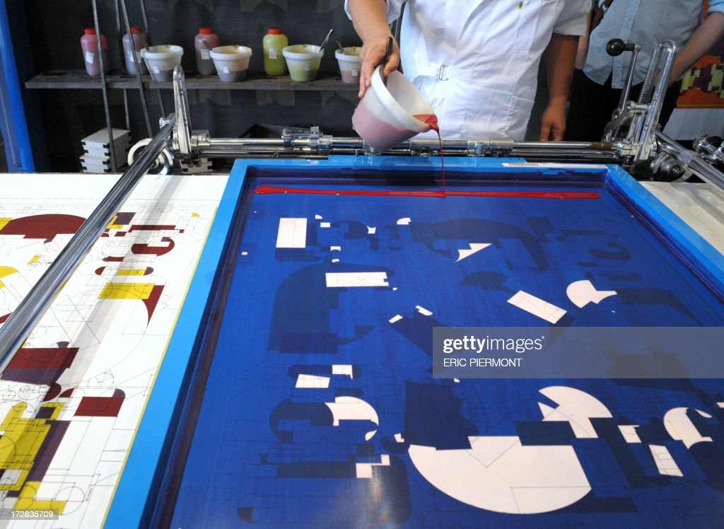 A textile craft specialist shows the traditional Frame Printing or Lyonnaise printing, The craftsman prints each of the colours making up the design in turn (frame by frame) according to a very precise sequence, at a presentation at the Nissim de Camondo Museum in Paris on July 4, 2013 of textile crafts at French luxury goods group Hermes. During Haute Couture presentations, as part of the metiers d'arts workshops, Hermes Texile Holding based in Lyon, presents five textile crafts, Engraving, Frame-printing or Lyonnaise printing, warp printing, hand-cut silk au Sabre and Linking. AFP PHOTO ERIC PIERMONT