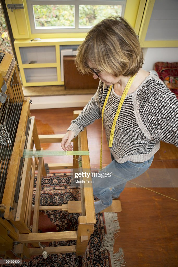 Textile designer weaving on a loom : Stock Photo