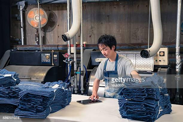textile industry worker checking inventory with digital tablet before shipping
