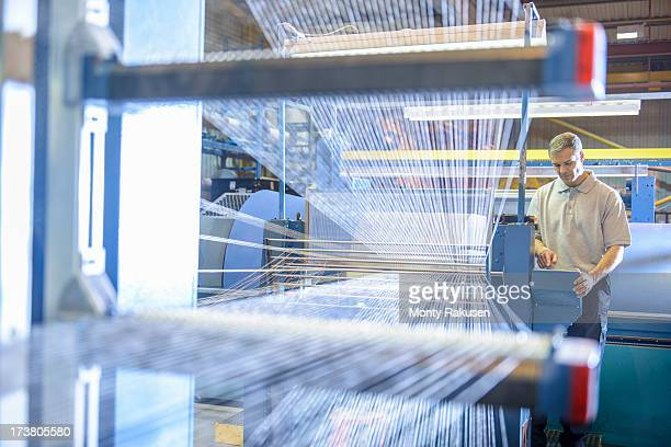Textile worker inspecting threads on loom in mill
