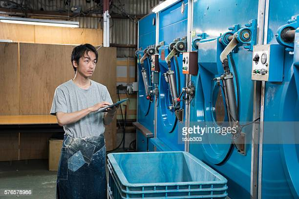 Textile worker using a digital tablet in a washing plant