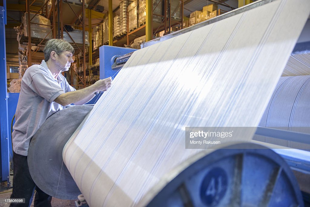 Textile worker winding yarn on industrial loom in mill