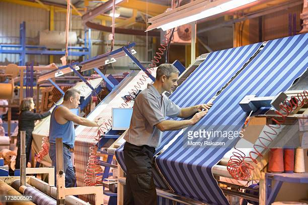 Textile workers inspecting striped woven thread in mill