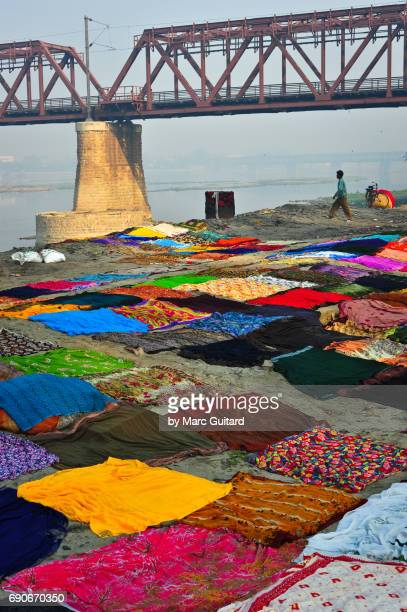 Textiles set up for drying beneath a train bridge on the banks of the Yamuna River. Agra, Uttar Pradesh, India